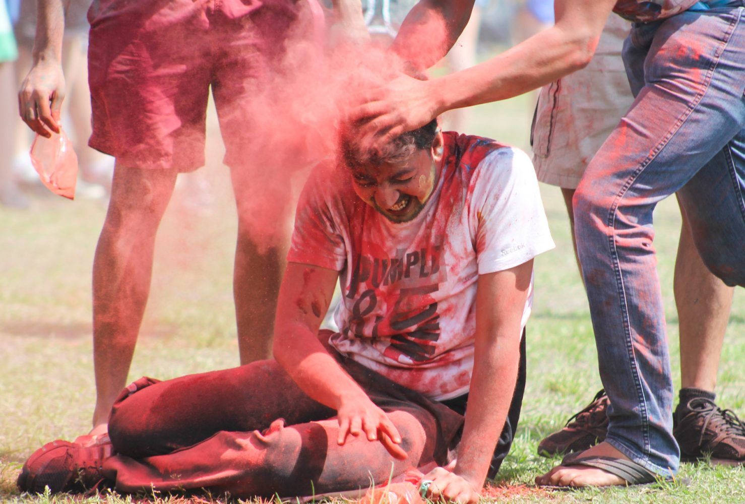 A man gets covered in red colored cornstarch while celebrating at the Holi festival.