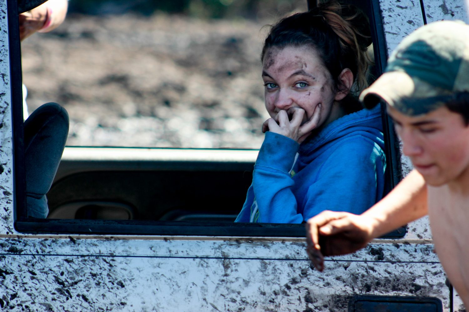 Rachel Caldwell, of Belleview, Fla., watches as her friends try to retrieve their truck from the mud on the Hog Waller property on Sunday afternoon, March 2, 2014.