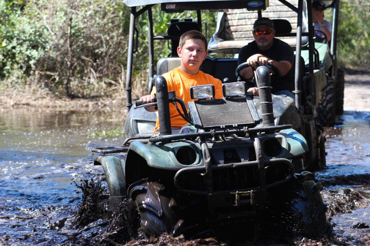 Dustin Carter, 14, rides through a mud hole with his family on the Hog Waller property on Sunday afternoon, March 2, 2014.