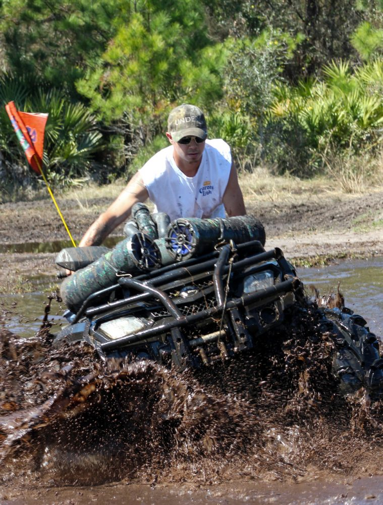 Jesse Brooks of Interlaken, Fla. drives through a mud hole on the Hog Waller property on Sunday afternoon, March 2, 2014.