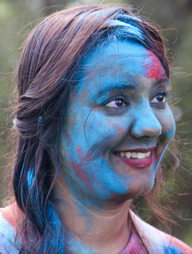 A woman is covered in colored cornstarch at the end of the festival.