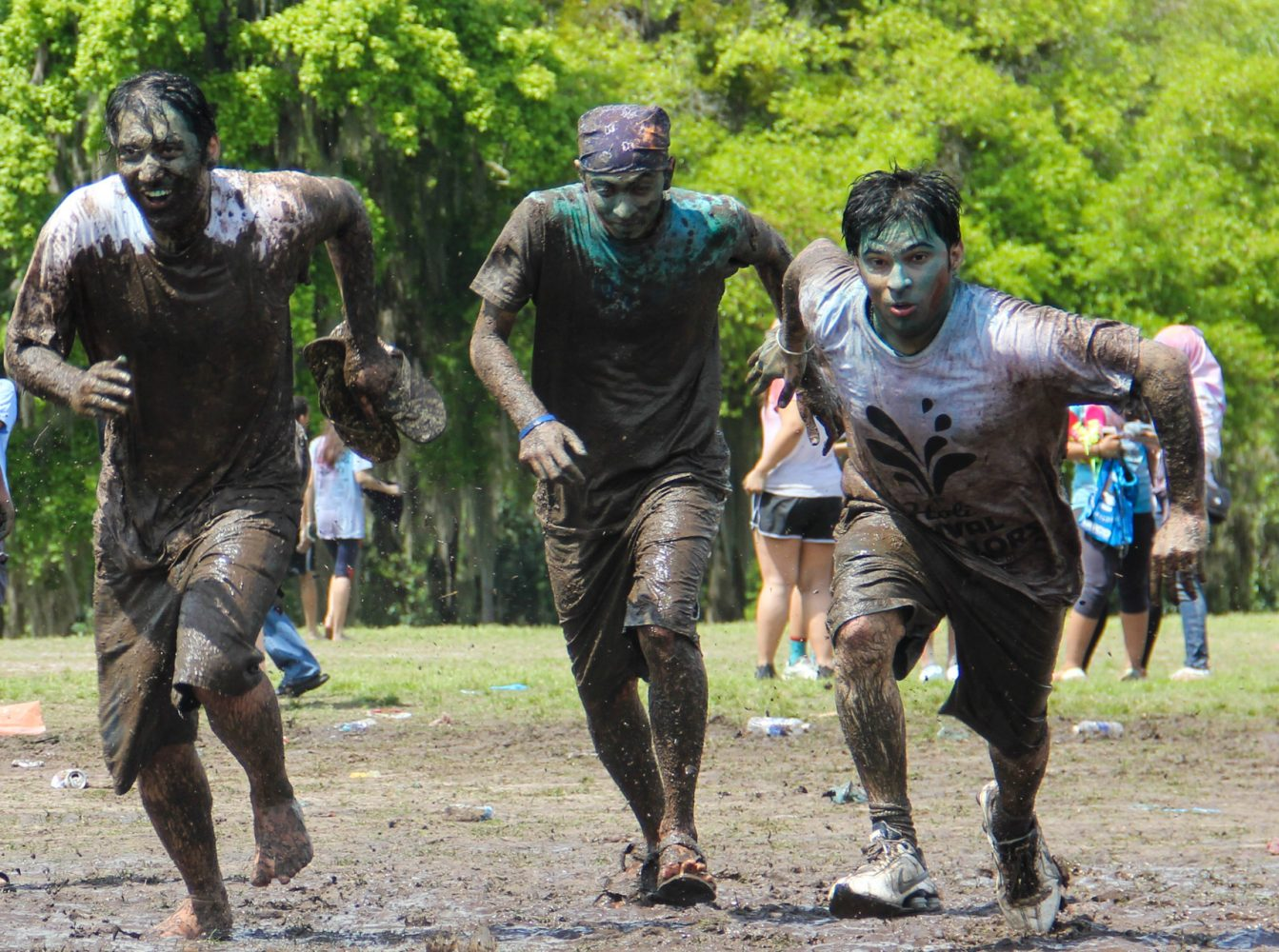 A group of friends dive into the mud at the culmination of the Holi festival.