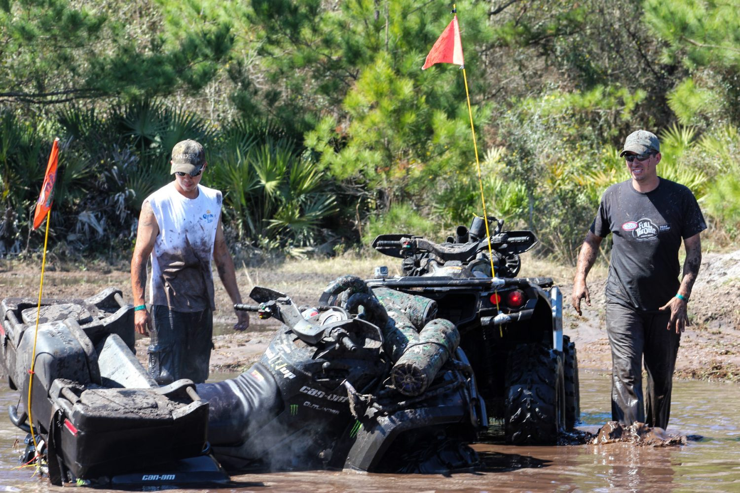Jesse Brooks, left, looks at his four-wheeler that got stuck in the mud as his friend, Patrick Anthony, comes to his aide on Sunday afternoon, March 2, 2014.