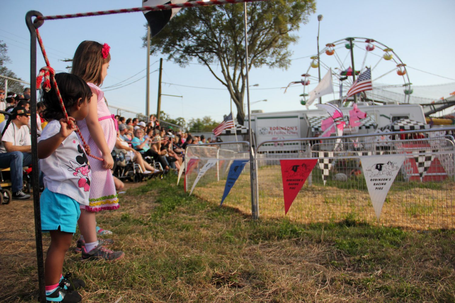 Two girls wait for the Robinson's Pig Race to begin at the Florida Strawberry Festival on Sunday afternoon. Mar. 9, 2014. The pigs are coaxed to race around the track with the aid of Oreo cookies.
