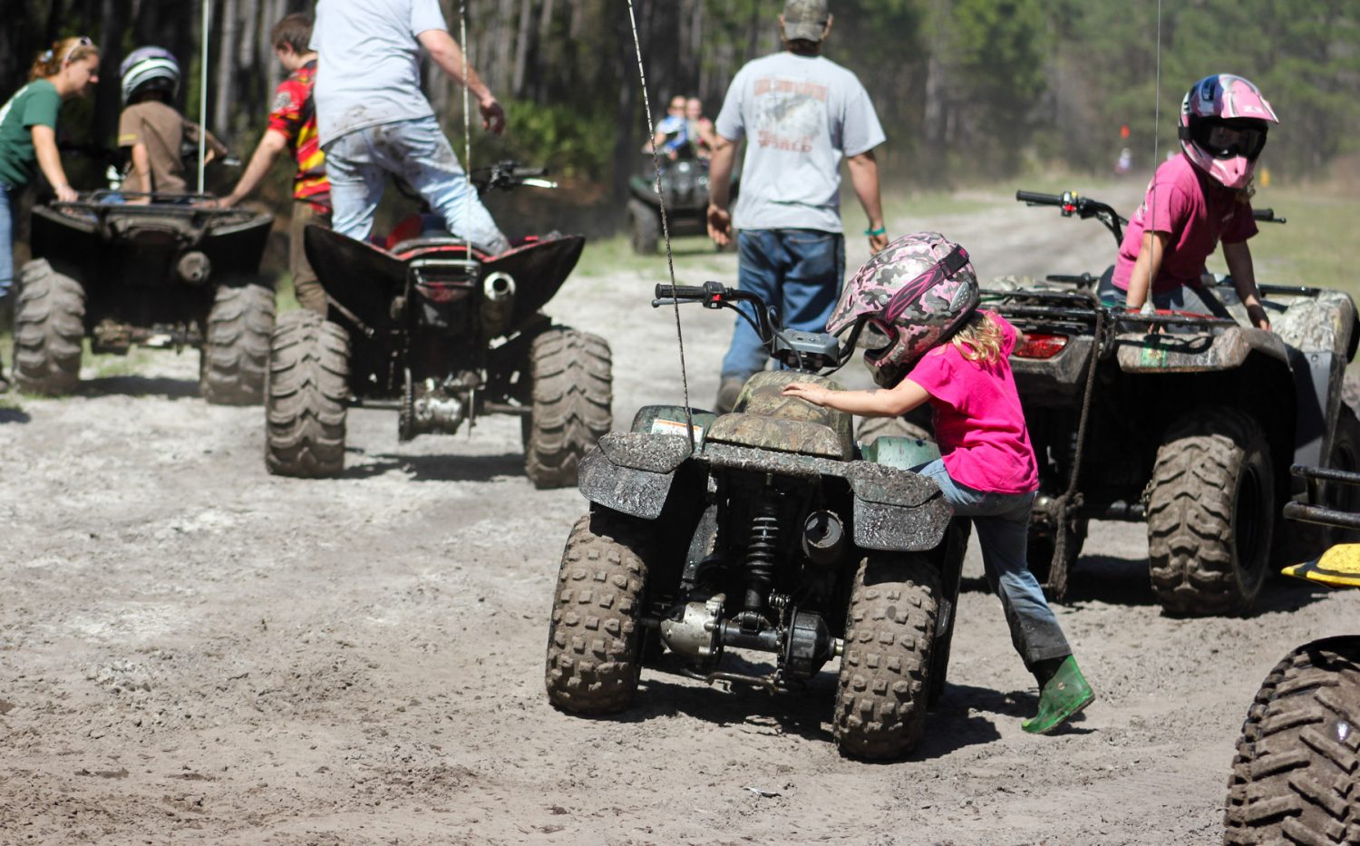 A young girl rides a child-sized four-wheeler with her family on the Hog Waller property on Sunday afternoon, March 2, 2014.