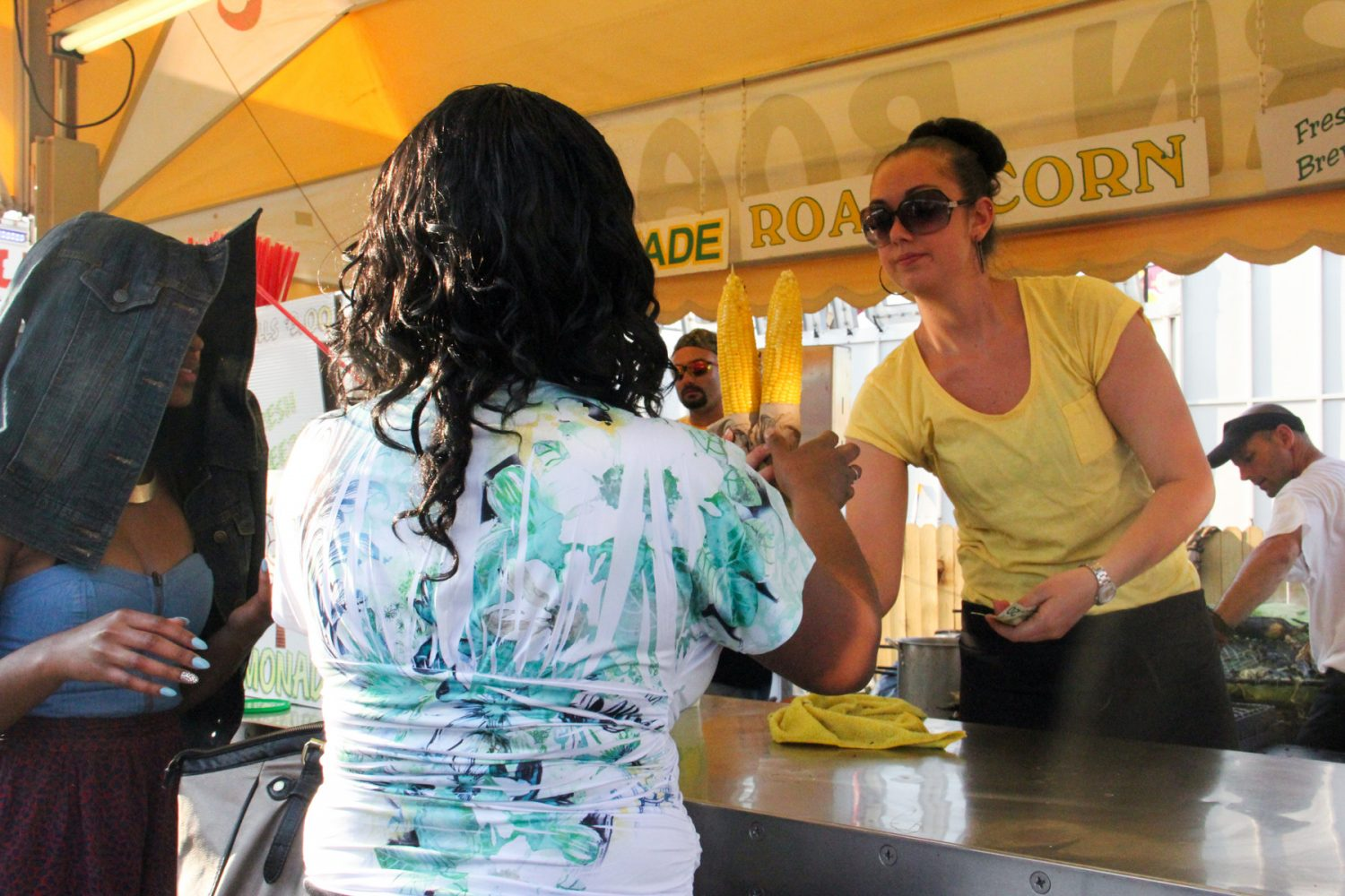 A vendor hands a customer two ears of buttered corn at the Florida Strawberry Festival on Sunday afternoon, Mar. 9, 2014. Also sold at the festival were turkey legs, gyros, fried butter and fresh squeezed lemonade.