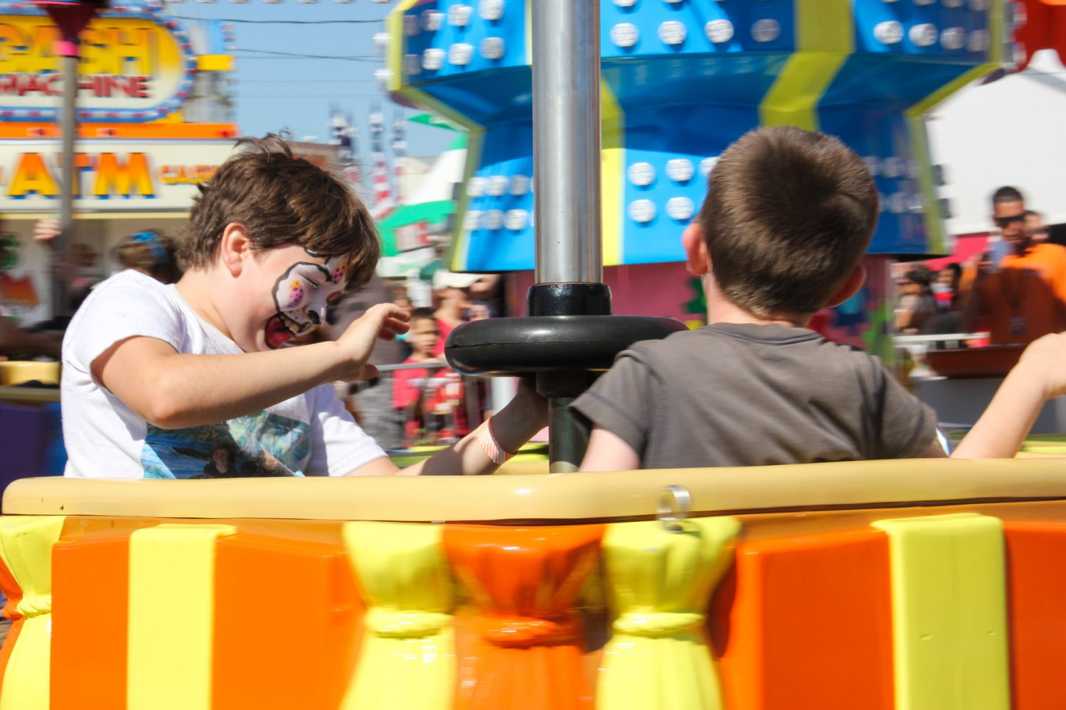 10-year-old Kaleigh, left, and her brother Kyle, 5, ride on a carnival ride at the Florida Strawberry Festival on Sunday afternoon, Mar. 9, 2014