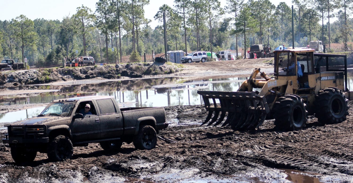 A John Deere backhoe assists a truck that got stuck in the mud pit at Hog Waller in Palatka, Fla. on Sunday afternoon, March 2, 2014. The Pit is six acres in size and is 10 feet below ground level.
