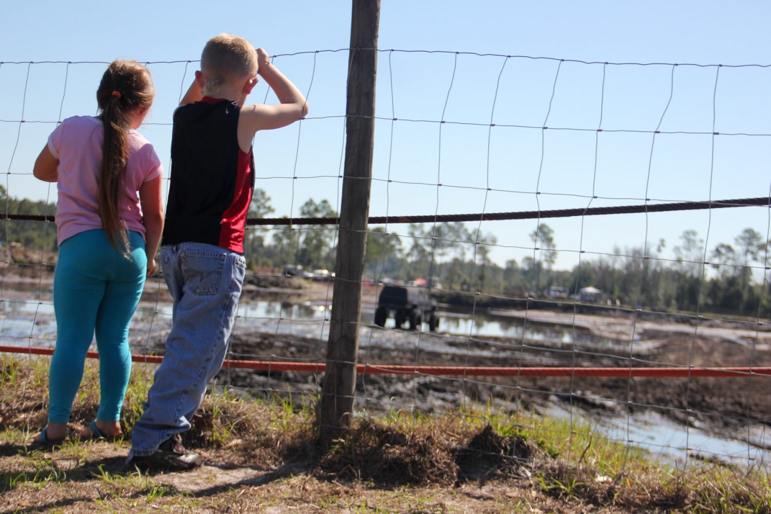 Children watch as a truck races through the mud pit at Hog Waller in Palatka, Fla. on Sunday afternoon, March 2, 2014.