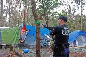 William Gough, a Gainesville Police Department officer, tags a tree with green spray paint in order to color-coordinate sections of Sweetwater Branch, a homeless community, during a zoning initiative implemented to improve emergency response times to homeless communities.