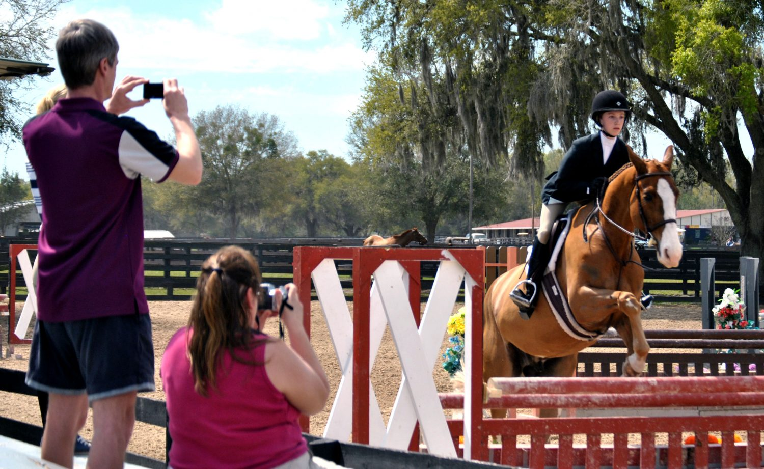 Heather Musson, 14-year-old equistrian from Ontario, shows her new horse, Crackerjack, as her family captures her performance. HITS is Musson's first international competition, and she was named Reserve Champion on Sunday.