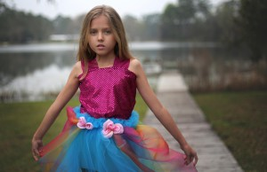 Lily Tallerico, 9, poses outside of her Palatka house in one of the new gowns in her fashion line that will debut Saturday at the Fashion for Freedom runway show. This dress, inspired by the queen of all colors, is Lily's favorite out of her line of eight dresses.
