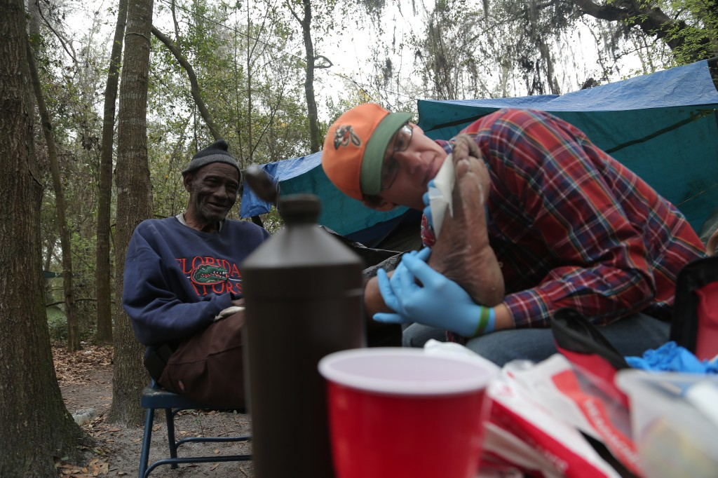 Roosevelt Anderson, a Tent City resident, receives care from Alex Templeton. Templeton is a traveling Catholic missionary who spent three months in Gainesville providing service to the less fortunate.