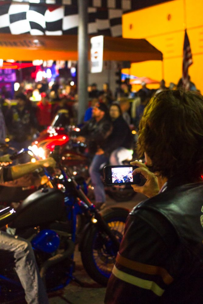 A woman records a video as motorcycle riders pass by on Main Street during the 73rd annual Bike Week in Daytona Beach on Friday, March 14.