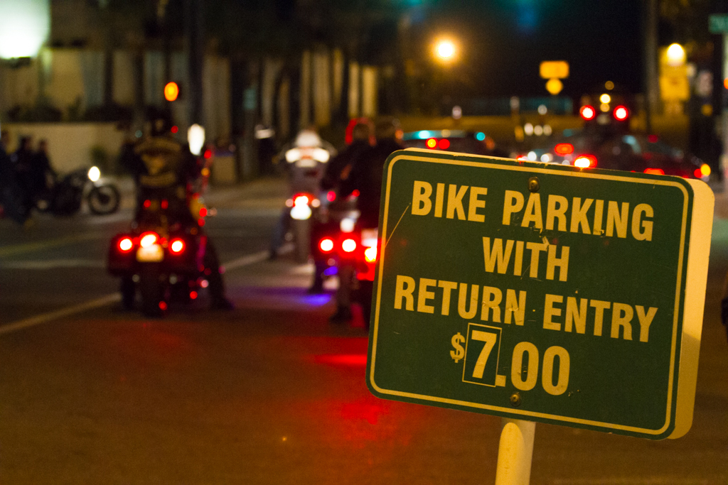 A group of motorycle riders wait at a stoplight beyond a sign advertising motorcyle parking during the 73rd annual Bike Week in Daytona Beach on Friday, March 14.