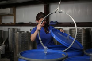 Brittany Gann works with a barrel of local blueberry wine in Bluefield Estate Winery Thursday.