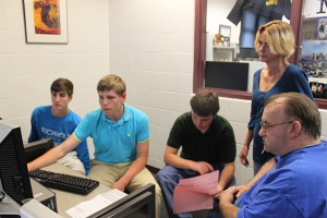 (Left to right) Ryan Warm, 15, watches as Blake Williams, 15, and Zach McAfee, 14, prepare Dawn Walker and William Walker's 2013 taxes. Eighty-seven Buchholz Academy of Finance students are certified tax preparers and volunteer at their computer lab on Tuesdays as a United Way Volunteer Income Tax Assistance site.