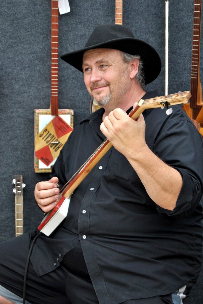 James Floyd, a designer from Pensacola, makes music from a cookie tin as he showcases his multidisciplinary art at the Santa Fe College Springs Arts Festival Sunday.