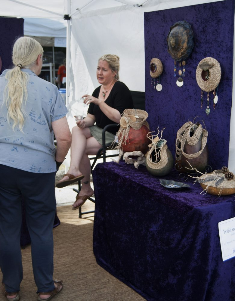 Whitney Powell of Tallahassee explains her 3-D Mixed Media work at the Santa Fe College Springs Arts Festival Sunday.