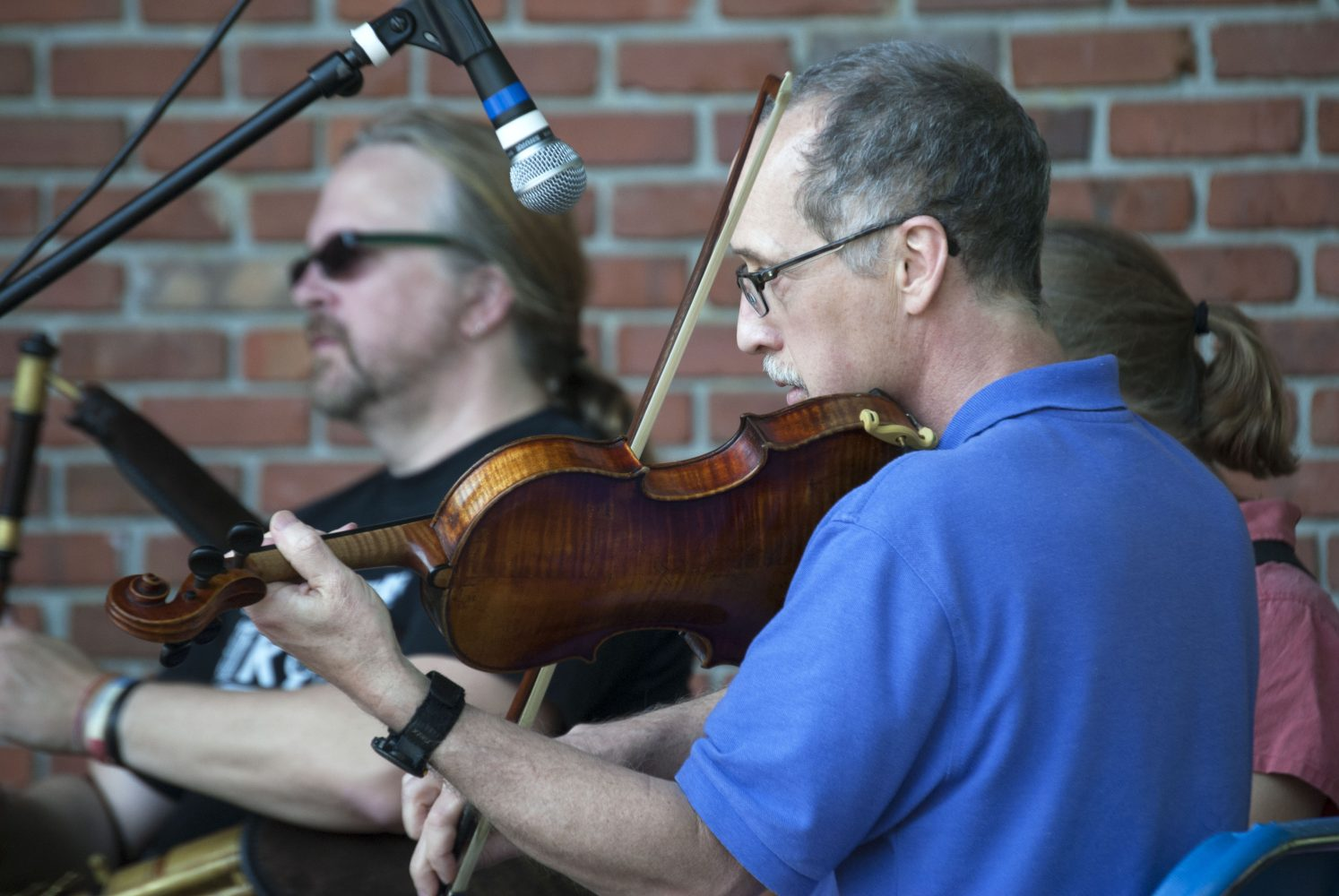 James Sheppard (front) plays the fiddle with a local band at the Viva Europe Festival at Bo Diddley Community Plaza Sunday.
