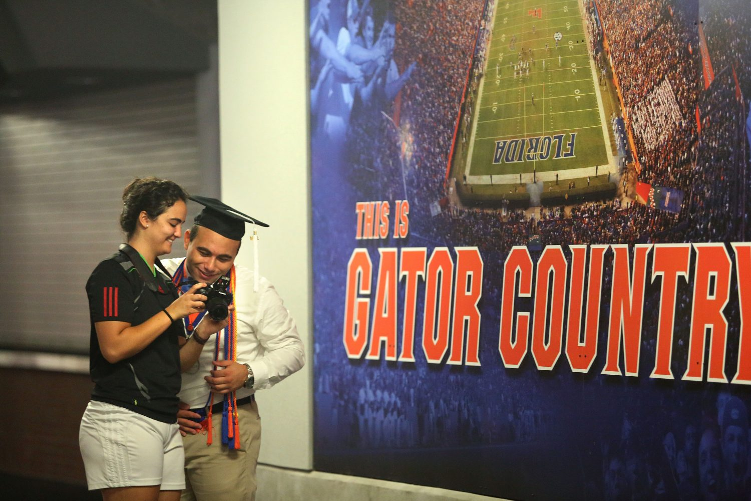 Greg Cohen, 22, looks at the photos taken by Katie Sastre, 20, for his graduation shoot at Ben Hill Griffin Stadium at the University of Florida on Thursday, May 1, 2014, in Gainesville, Fla. Cohen will graduate with a B.A. in economics.