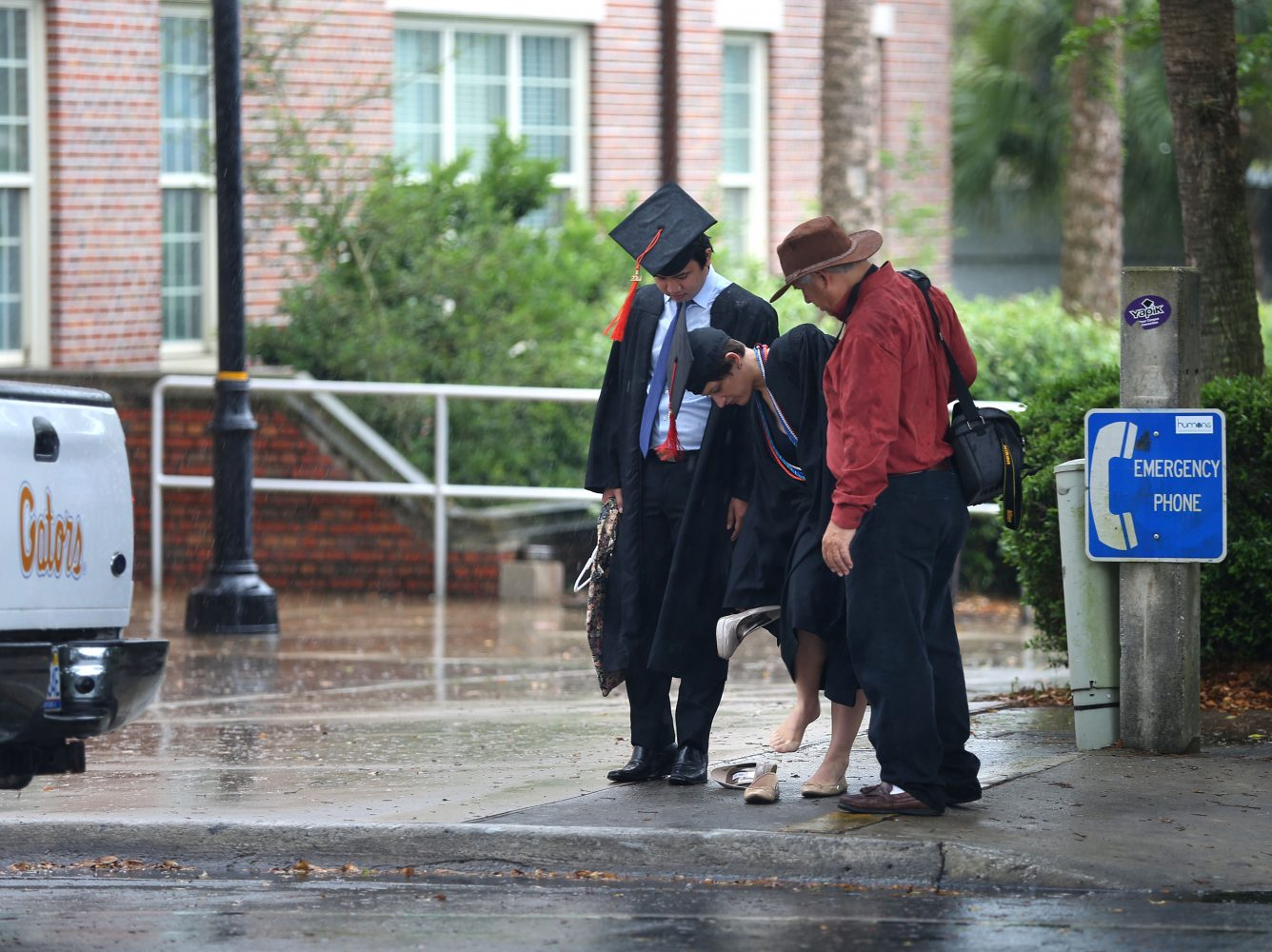 A graduate takes off her heels as the rain pours down on Stadium Road at the University of Florida on Thursday, May 1, 2014, in Gainesville, Fla.