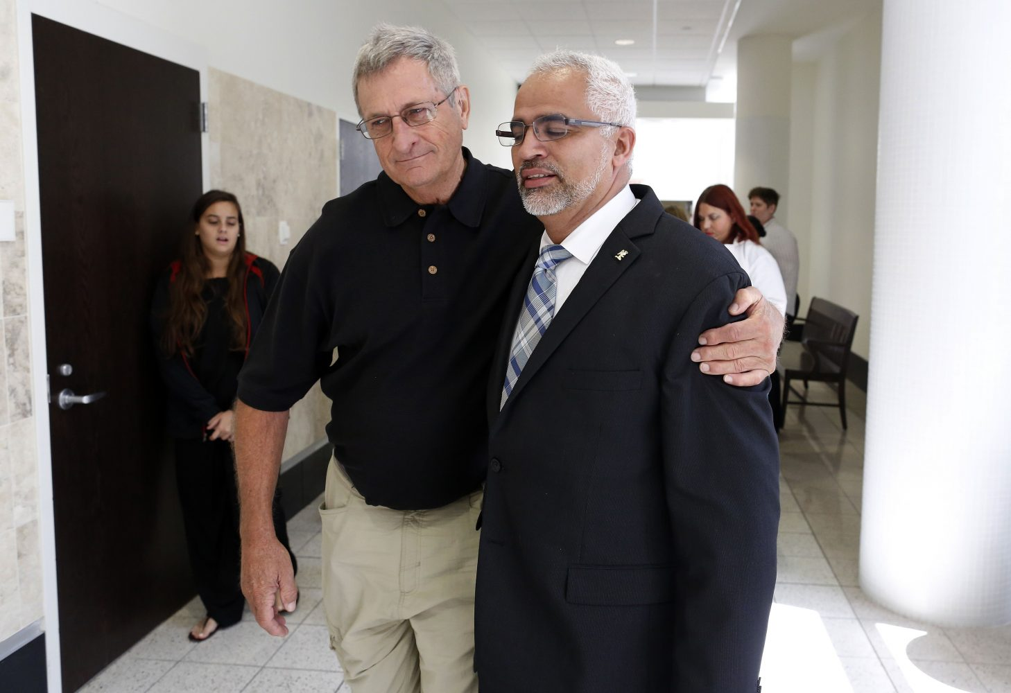 """Carlos Aguilar, the father of Christian Aguilar, is hugged by family friend Tom Tumbleson during a lunch recess following the prosecution's opening statements in the case against Pedro Bravo in courtroom 1B of the Alachua County Criminal Justice Center Tuesday, August 5, 2014.  Aguilar said Tumbleson is his """"Angel"""", because he was the first person to contact them and look for Christian.  Bravo is accused of murdering his son.  (Doug Finger/The Gainesville Sun/Pool)"""