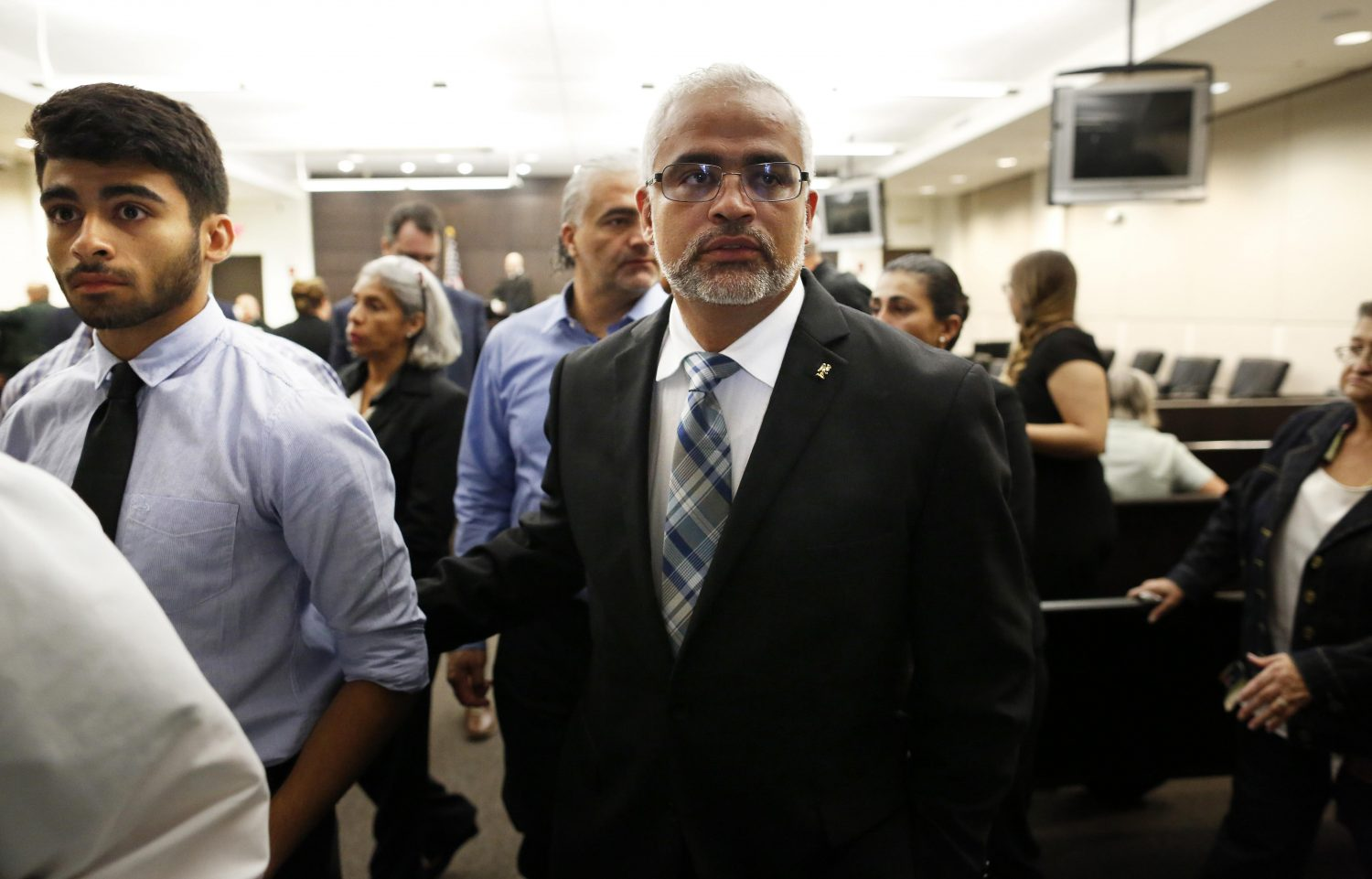 Carlos Aguilar, the father of Christian Aguilar, leaves the courtroom with his son Alex for a lunch recess following the prosecution's  opening statements in the case against Pedro Bravo in courtroom 1B of the Alachua County Criminal Justice Center Tuesday, August 5, 2014.  (Doug Finger/The Gainesville Sun/Pool)
