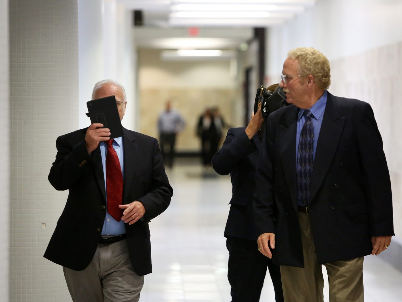 The parents of Pedro Bravo shield their faces from the camera as they walk back to the courtroom for their son's murder trial at the Alachua County Criminal Justice Center Tuesday, August 5, 2014.  Pedro is accused of killing friend and University of Florida student Christian Aguilar.  (Doug Finger/The Gainesville Sun/Pool)