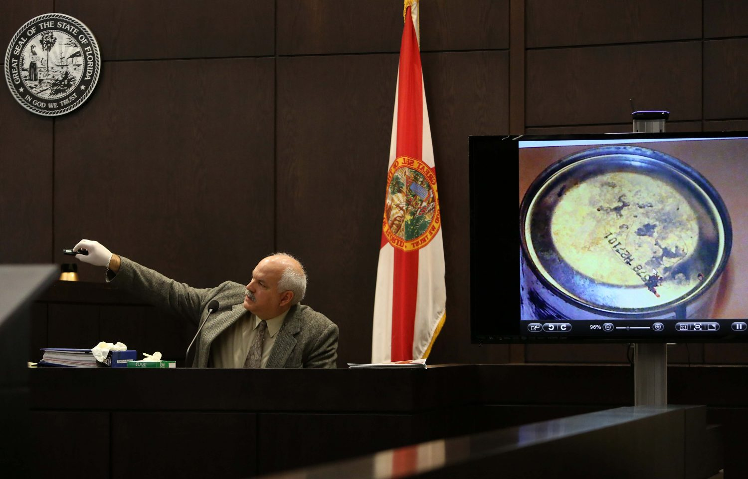 Gainesville Police Crime Scene Investigator Mark Trahan points to blood found on the bottom of a Rust-Oleum paint can that was found during a search of Pedro Bravo's Chevy Blazer in courtroom 1B of the Alachua County Criminal Justice Center Thursday, August 7, 2014.  Bravo is accused of killing University of Florida student Christian Aguilar.  (Doug Finger/The Gainesville Sun/Pool)