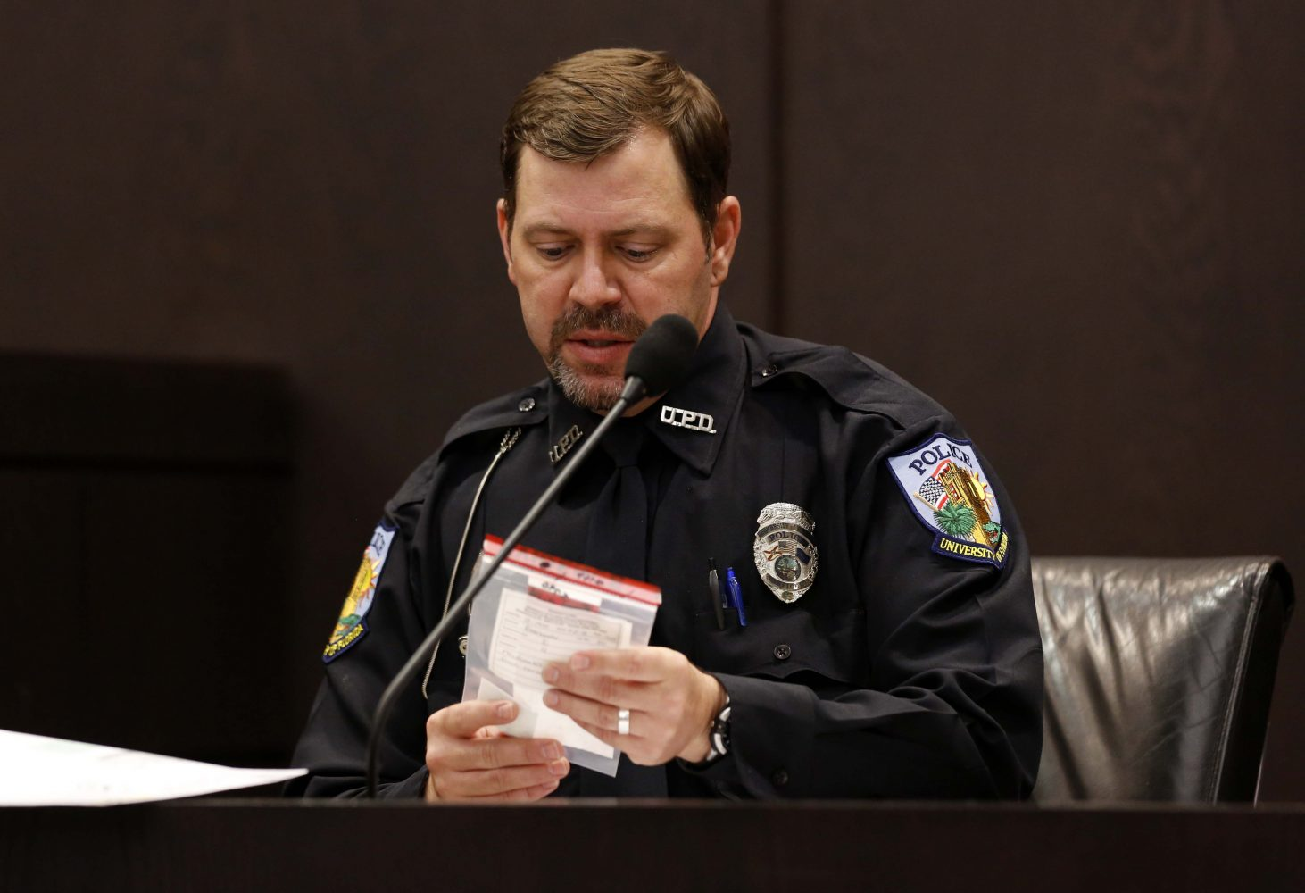 University Police Officer Tim Peck verifies a McDonald's receipt found in Pedro Bravo's Chevy Blazer for prosecutor Brian Kramer during Bravo's murder trial in courtroom 1B of the Alachua County Criminal Justice Center Friday, August 8, 2014.  Bravo is accused of killing University of Florida student Christian Aguilar.  (Doug Finger/The Gainesville Sun/Pool)