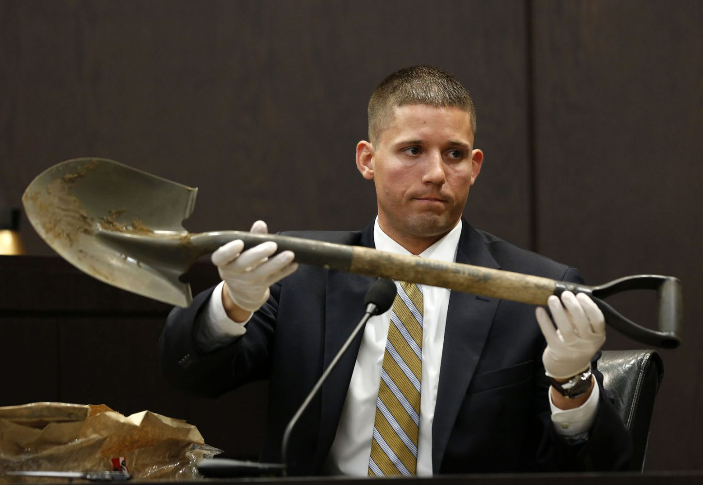 Assistant State Attorney Christopher Elsey shows the jury the shovel that was found at Spyglass apartments during Pedro Bravo's murder trial in courtroom 1B of the Alachua County Criminal Justice Center Thursday, August 14, 2014.  Bravo is accused of killing University of Florida student Christian Aguilar.  (Doug Finger/The Gainesville Sun/Pool)