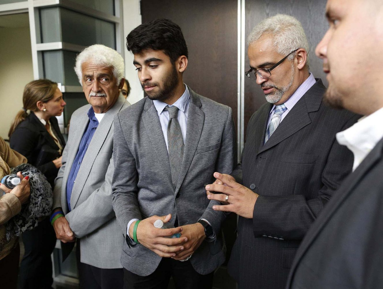 Alex and Carlos Aguilar, the brother and father of slain University of Florida student Christian Aguilar, from left at center, wait outside the courtroom following a lunch break during Pedro Bravo's murder trial at the Alachua County Criminal Justice Center Friday, August 15, 2014.  Bravo is accused of killing University of Florida student Christian Aguilar.  (Doug Finger/The Gainesville Sun/Pool)