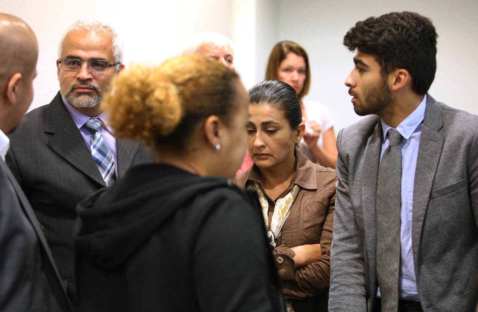 The Aguilar family, from left facing, Carlos, Claudia and Alex, talk about defense attorney Michael Ruppert's closing statements during a brief recess in Pedro Bravo's murder trial in courtroom 1B of the Alachua County Criminal Justice Center Friday, August 15, 2014.  Bravo is accused of killing University of Florida student Christian Aguilar.  (Doug Finger/The Gainesville Sun/Pool)