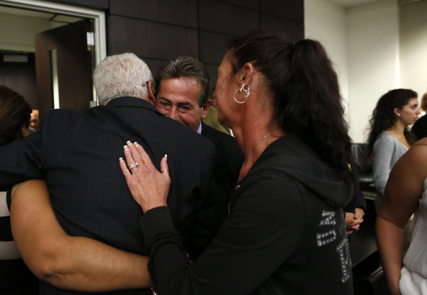 Lead detective Randy Roberts with the Gainesville Police Department, at center facing, hugs Carlos Aguilar, the father of slain University of Florida student Christian Aguilar, after Christian's killer Pedro Bravo was found guilty of first degree murder in courtroom 1B of the Alachua County Criminal Justice Center Friday, August 15, 2014.   (Doug Finger/The Gainesville Sun/Pool)