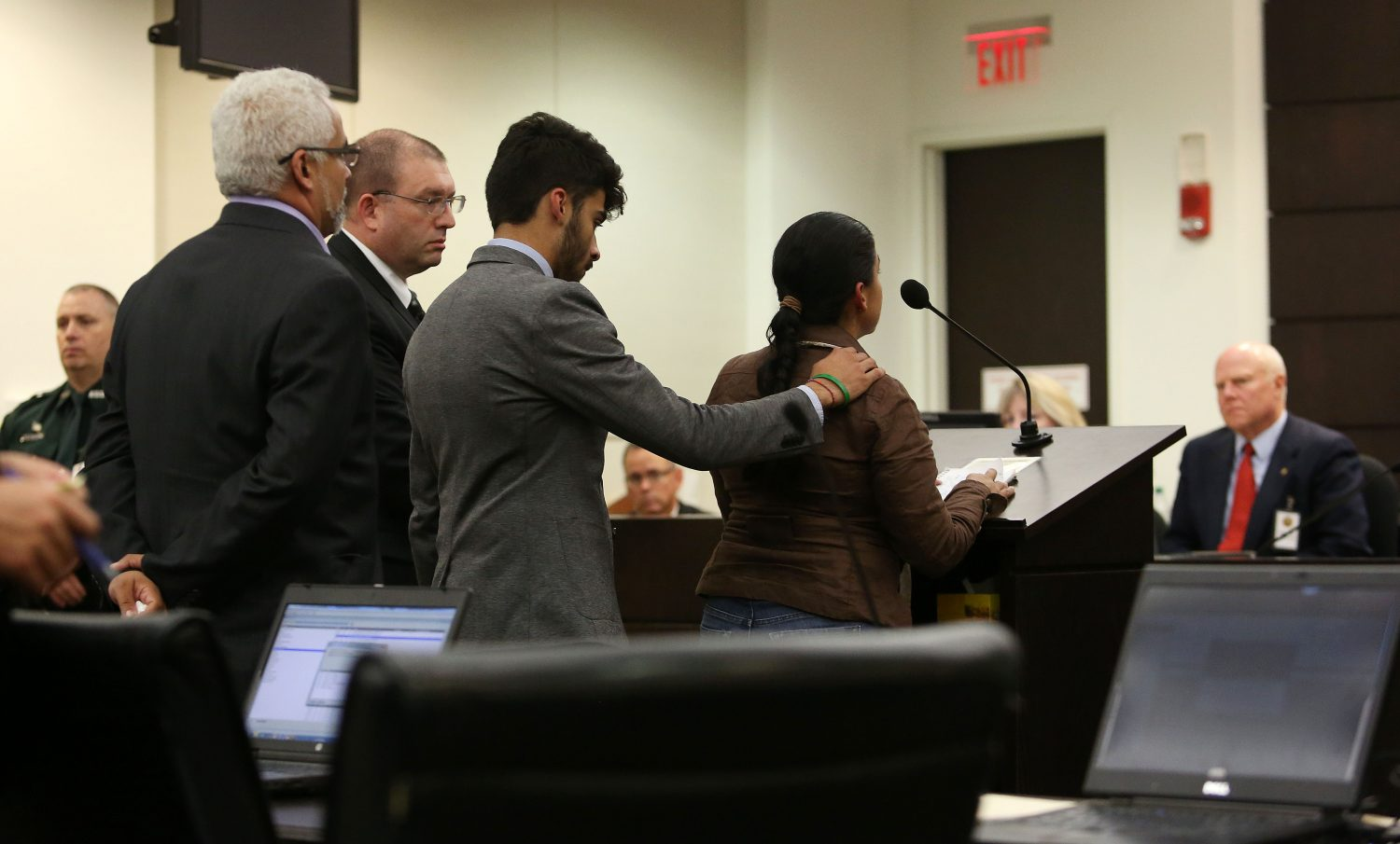 Alex Aguilar comforts his mother Claudia as she speaks to Circuit Court Judge James Colaw before Pedro Bravo's sentencing for the first degree murder of her son Christian in courtroom 1B of the Alachua County Criminal Justice Center Friday, August 15, 2014.  At left are Christian's father Carlos and lead prosecutor Brian Kramer.  (Doug Finger/The Gainesville Sun/Pool)