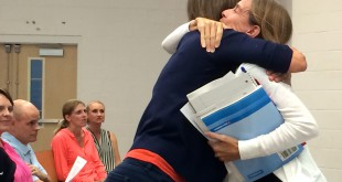 Susan Bowles hugs Jennifer Anhalt after Anhalt roused the crowd at the town hall meeting Tuesday night regarding standardized test practices in in Alachua County. In an interview after the meeting, Bowles said she was so grateful to have heard Anhalt speak with such skill on the matter that is so close to the hearts of many teachers.