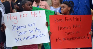 Twins Jada and Jaelyn Weems spend their birthday holding signs during the vigil. They live close to Ocala Place Apartments, where some of the shootings have occurred.
