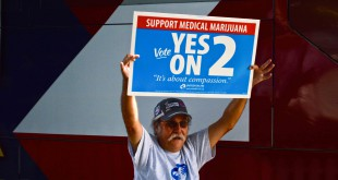 "Steve McGriff, 63, from Hog Valley, Fla., waves a sign showing support for Medical Marijuana outside of John Morgan's ""Yes On 2"" bus on Sept. 10, 2014."