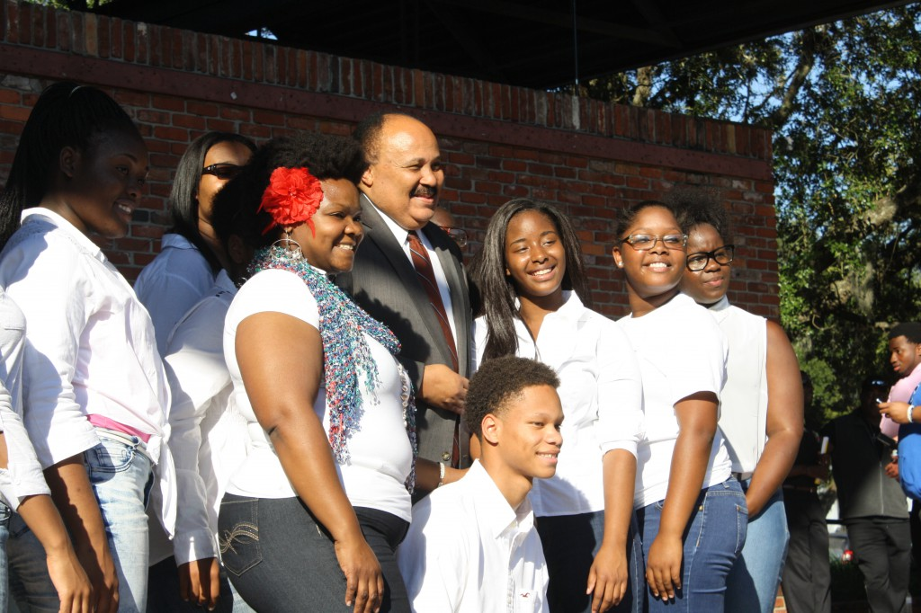 "Martin Luther King III poses for photos with Eastside High School's Gospel Choir before addressing the crowd of voters at the Bo Diddley Community Plaza. ""My father used to say that a voteless people is a powerless people,"" he said. ""One of the most important steps we can take is the step to the ballot box."""