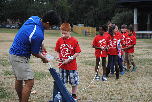 Vincent, a fourth grade student from Idylwild Elementary School helps aerospace engineering student Cesar Santoyo set up a water rocket. Fourth and fifth grade students from Idylwild Elementary School visited the University of Florida on Oct. 30 to learn about engineering and other STEM-related studies.