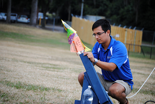 Cesar Santoyo, 19, an aerospace engineering student at the University of Florida, sets up a water rocket at Flavet Field. Fourth and fifth grade students from Idylwild Elementary School visited the University of Florida on Oct. 30 to learn about engineering and other STEM-related studies.