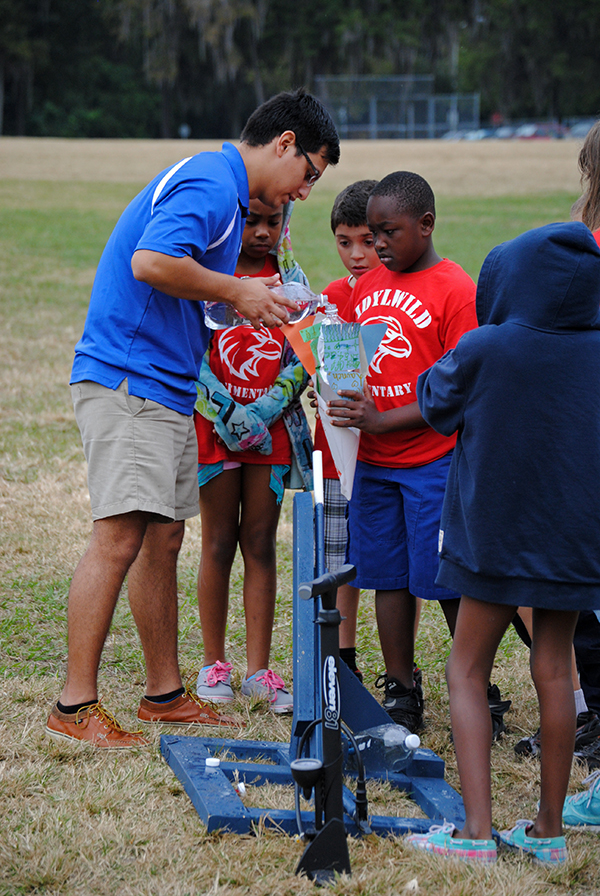 Cesar Santoyo, 19, an aerospace engineering student, helps students from Idylwild Elementary School set up a water rocket at Flavet Field. Fourth and fifth grade students from Idylwild Elementary School visited the University of Florida on Oct. 30 to learn about engineering and other STEM-related studies.