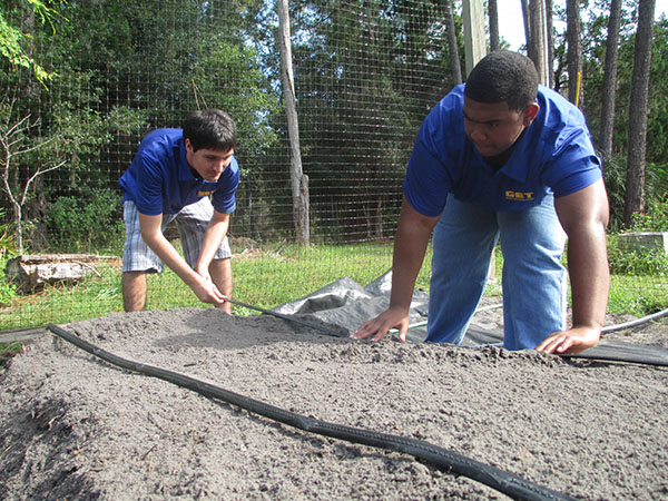 Tudorel Tomlin, 21, (left) and Arthur Seabrooks, 17, (right) lay irrigation tape in the herb garden. The system replaces sprinklers that over-watered certain areas of the garden and left others parched.