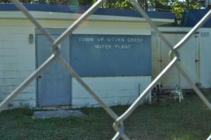 Otter Creek's water plant sits behind a chain link fence right next to Archer Road. To get the necessary clean drinking water the town needs, this plant would have to be replaced with a more advanced system to rid the well water of its contaminants.