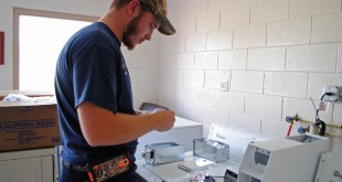Seth Hansford, an installation technician with Southeastern Laundry Equipment, installs a new washer at Grace Marketplace. Grace Marketplace received six washers, six dryers and one large commercial washer, on Thursday, Nov. 6.