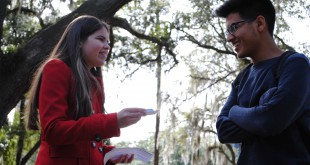 Freshman Roxana Bonachea gives a flier on quitting tobacco to a student. Volunteers and UF faculty and staff manned tables on campus for the Great American Smokeout on Nov. 20.