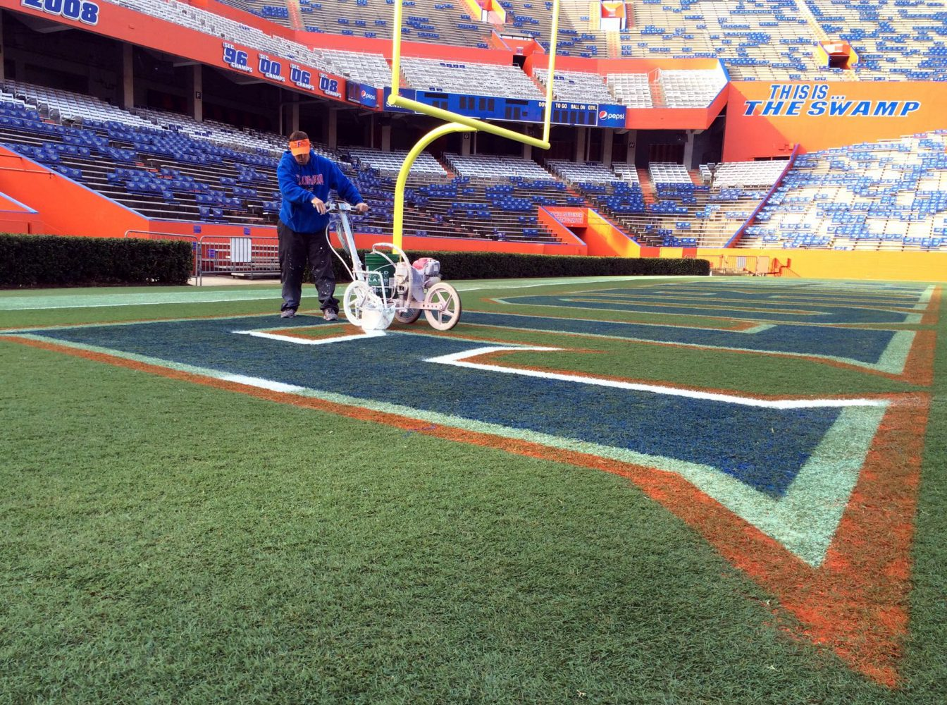 florida s grass guy cutting through the competition news jason smith turf coordinator rolls the first coat of white paint on the florida logo