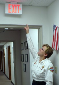 Assistant Fire Chief JoAnne Rice inspects an emergency exit sign outside her office at Gainesville Fire Rescue. Proper lighting, signage and open doorways are critical mainstays of a compliant fire inspection.