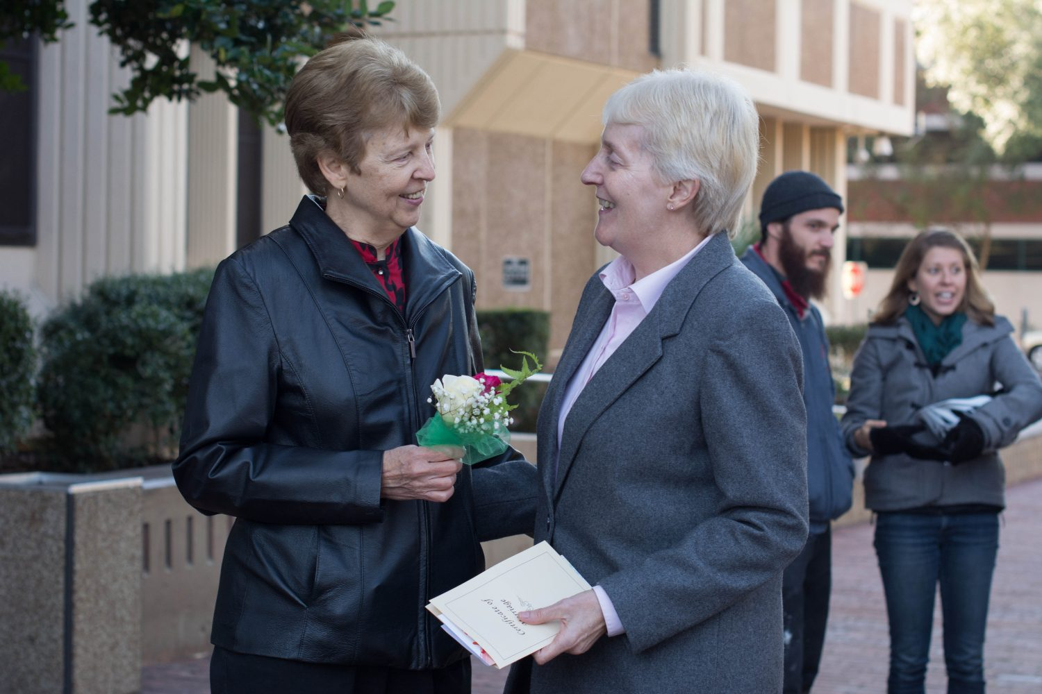 Karen Niederkohr (left) and Lola Yousey (right) celebrate their new marriage license on Tuesday, Jan. 6 outside the Alachua County Courthouse with a bouquet or fake flowers provided by the United Church of Gainesville.